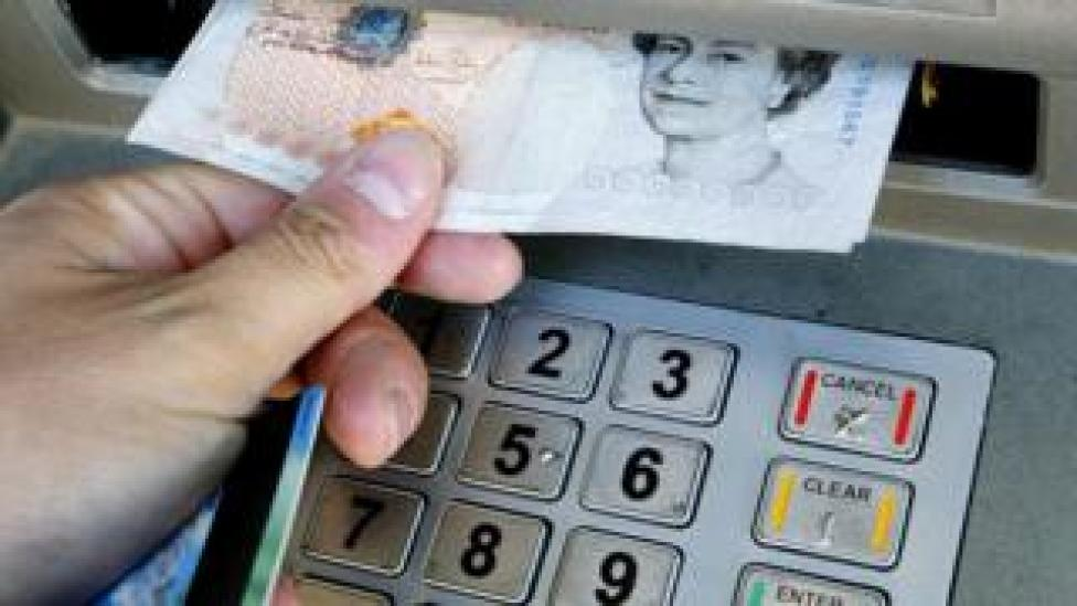 Close up of hand removing £10 from ATM