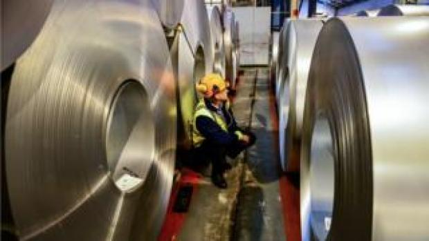 A worker inspects rolls of steel
