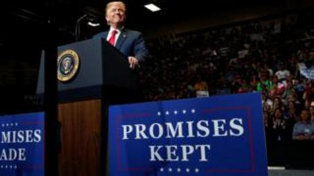 """U.S. President Donald Trump smiles at a rally with supporters next to a sign reading """"Promises Kept"""" at North Side middle school in Elkhart, Indiana, U.S. on 10 May 2018"""