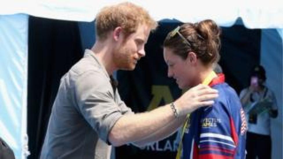 Prince Harry presents Elizabeth Marks with her medal