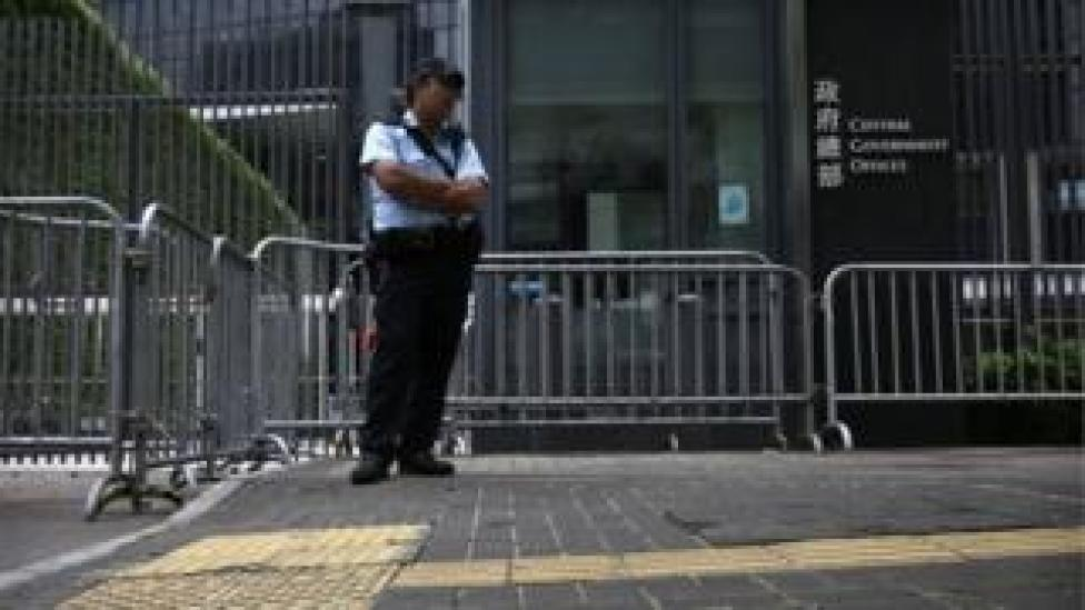 A policeman stands on pavement reinforced with glue to prevent the bricks from being dug up and used as projectiles during expected protests outside the central government offices in downtown Hong Kong on May 16, 2016