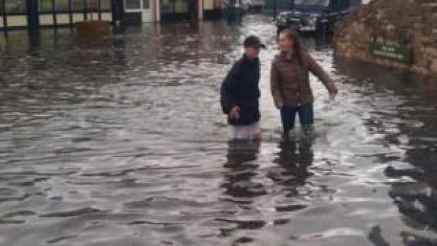 People wading through water on the flooded high street in Prestatyn