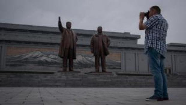 A tourist takes a photo of statues of late North Korean leaders Kim Il-Sung (L) and Kim Jong-Il (R), on Mansu hill in Pyongyang on July 23, 2017
