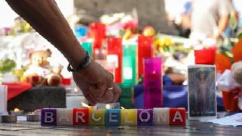 A man lights a candle in an impromptu memorial a day after a van crashed into pedestrians at Las Ramblas in Barcelona