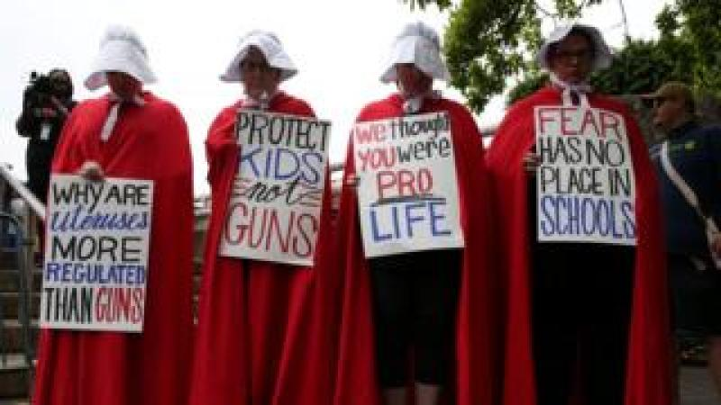 "Activists wear red robes and white bonnets based on ""The Handmaid's Tale"" before the ""March for Our Lives"""