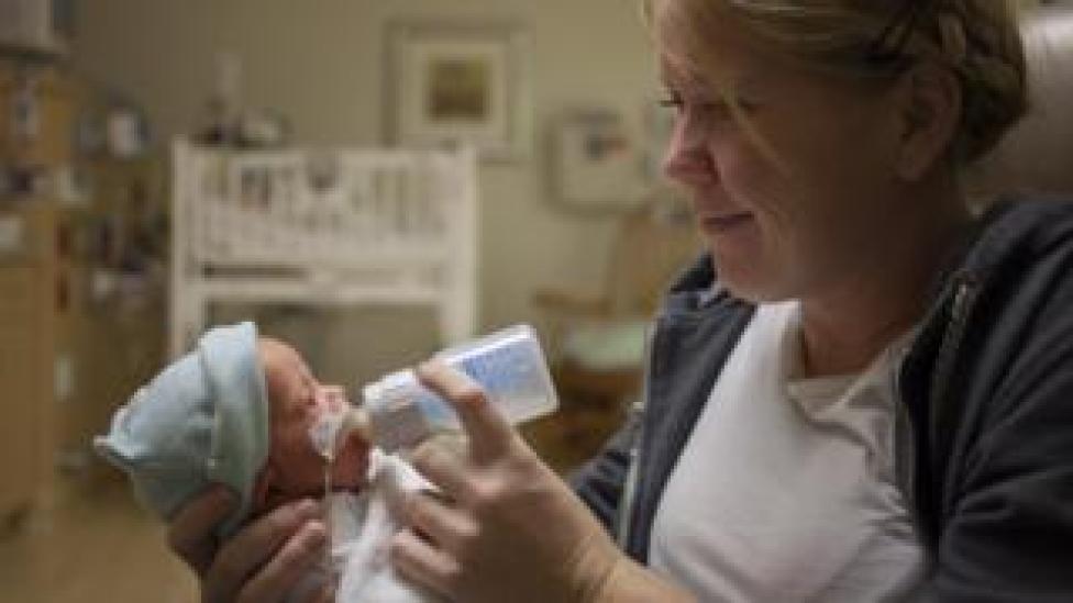 Mother feeding premature baby