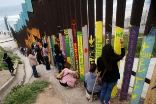 Mexican citizens paint on the border wall between Mexico and the United States in Tijuana, Mexico, 3 June 2017