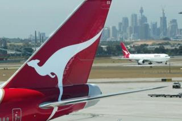 Qantas jets on the tarmac overlooking the city of Sydney