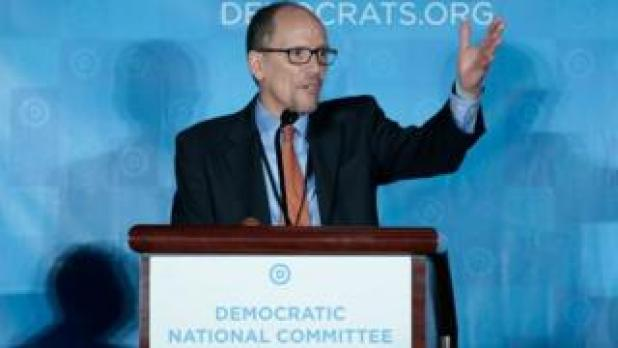 Tom Perez speaks to Democratic party delegates at a rostrum, his left hand raised in the air