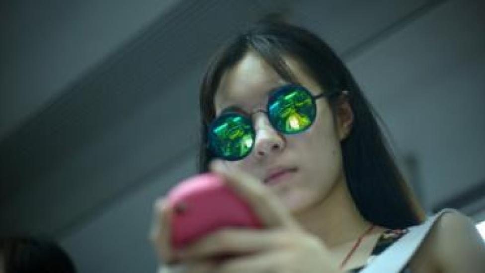 cep telefonuna bakan Çinli bir kadın