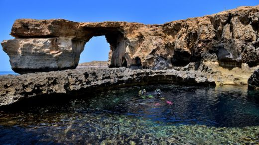 Divers are seen in front of the natural arch The Azure Window at Dwejra Bay on 20 May, 2014