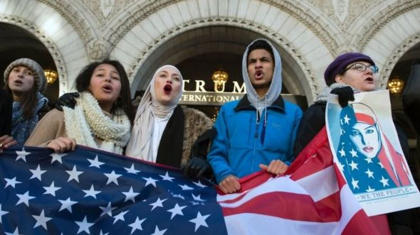 Protesters hold an US Flag while protesting outside the Trump Hotel in Washington DC. Photo: 4 February 2017