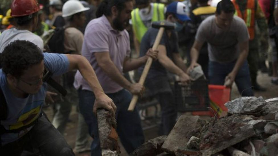 Rescuers and volunteers remove rubble and debris from a flattened building in search of survivors after a powerful quake in Mexico City on September 19, 2017.
