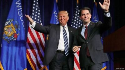 Republican presidential nominee Donald Trump (L) is welcomed to the stage by Wisconsin Governor Scott Walker