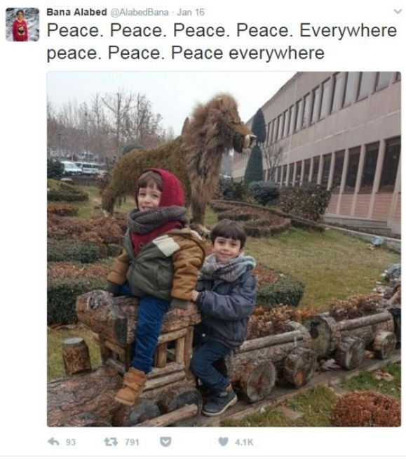 A screenshot from the Twitter account @AlabedBana, showing her two younger brothers smiling and seated on a a row of plant pots made in the shapes of a train. The caption reads
