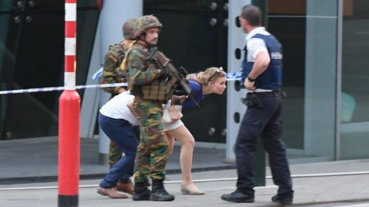 Soldiers and police officials guide members of the public on a street in Brussels, 20 June
