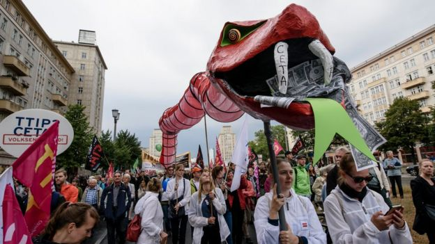 Protesters hold a giant snake with dollar notes in its mouth to demonstrate against the TTIP and CETA free trade agreements with a giant puppet on 17 September, 2016 in Berlin, Germany.