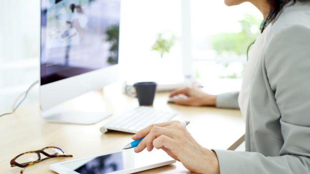 Mujer trabajando en una computadora en su casa.
