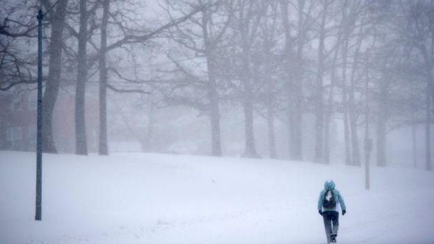 A pedestrian walks through snow in Parkville, Md., Saturday, Jan. 23, 2016.