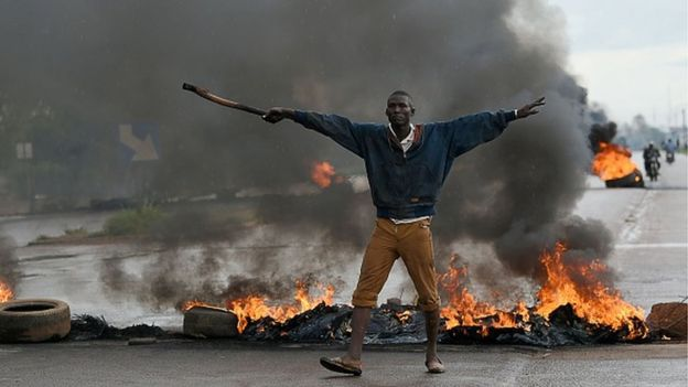 A man gestures as he stands in front of burning tyres on 19 September 2015 in Ouagadougou, Burkina Faso's capital.