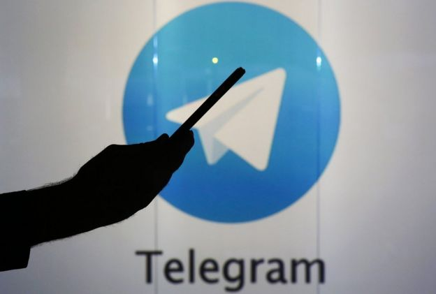 Un hombre sostiene el celular ante el logo de Telegram.