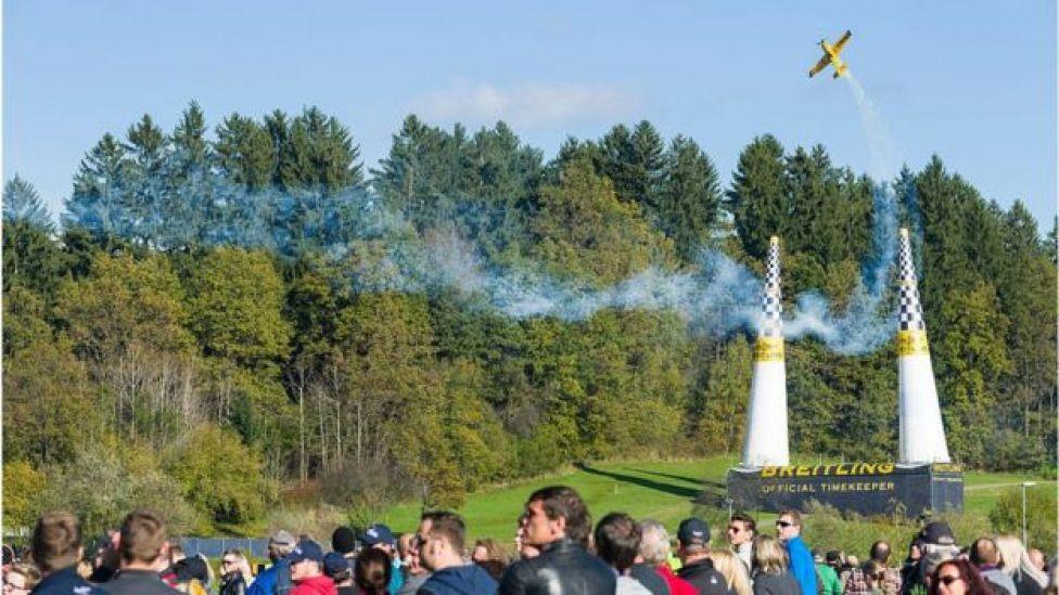 competencia de aviones de Red Bull que deja una estela de humo mientras pasa a través de 2 conos.