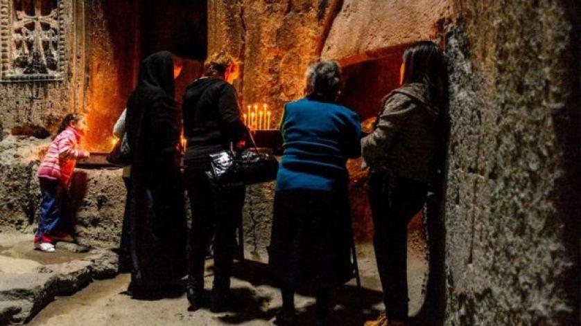 أربعة نساء يقفن أمام الشموع في كهف المصلين