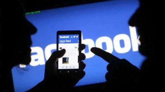 Imagem mostra duas pessoas lendo notícias no Facebook