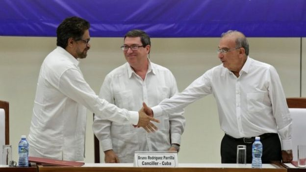 Colombia's FARC lead negotiator Ivan Marquez (L) and Colombia's lead government negotiator Humberto de la Calle (R) shake hands while Cuba's Foreign Minister Bruno Rodriguez looks on, after signing a final peace deal in Havana, Cuba, August 24, 2016.