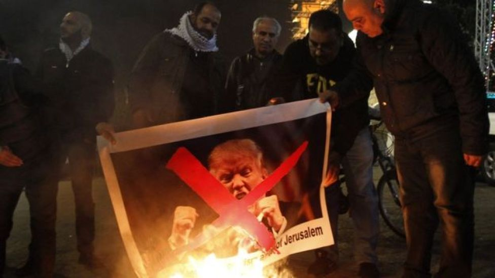 Palestinian protesters burn pictures of US President Donald Trump at the manger square in Bethlehem on December 5, 2017
