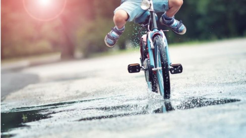 Chico montando bicicleta en charco