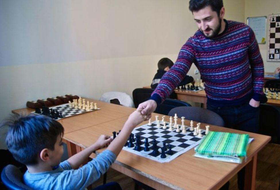 A teacher congratulates a young opponent