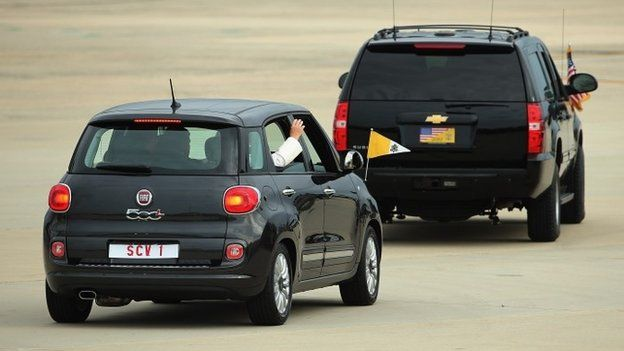 Pope Francis waves from the back of his Fiat