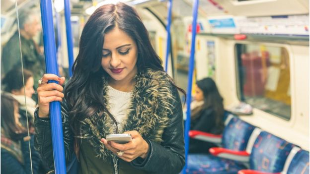 Woman using her mobile phone on an underground train