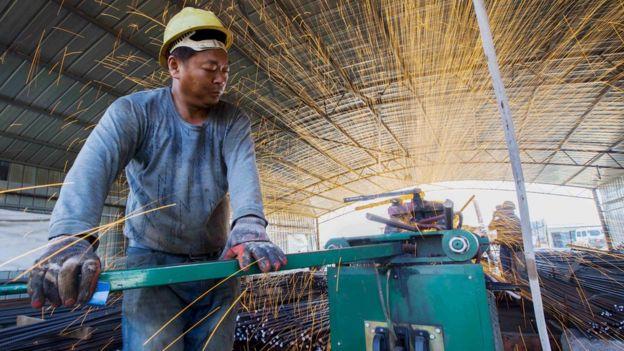 A labourer cuts steel bars at a railway bridge construction site in Lianyungang, Jiangsu province, China