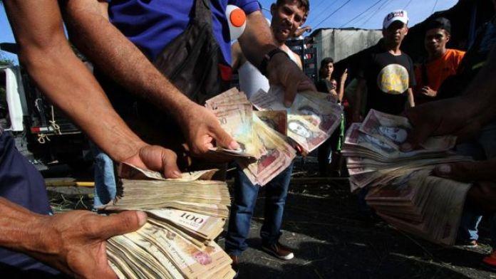 Hombres con billetes de 100 bolívares.