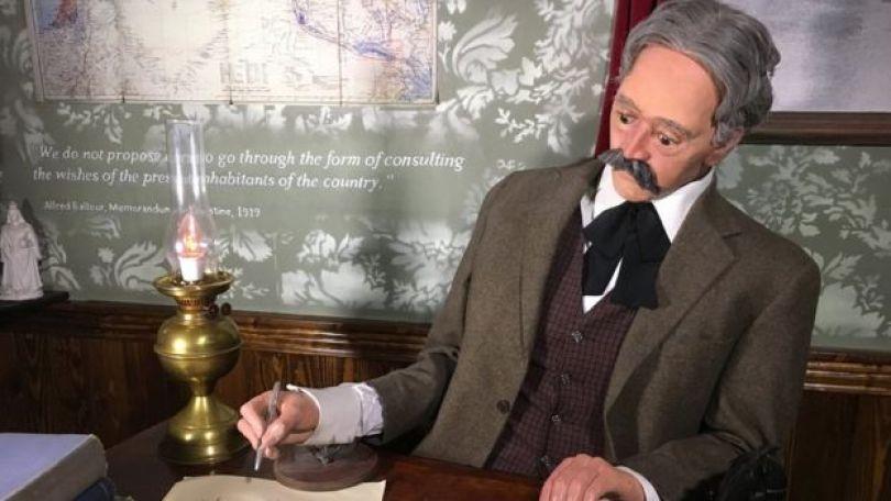 Boneco de Arthur Balfour assinando a declaração em um hotem em Belém