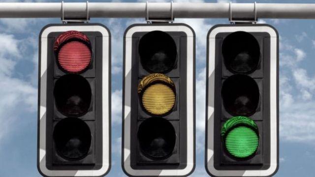 Tres semáforos alumbran en color rojo, amarillo y verde.