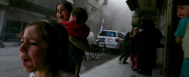 Ghazal, 4, (L) and Judy, 7, carrying 8-month-old Suhair, react after what activists said was shelling by forces loyal to Syria's President Bashar al-Assad near the Syrian Arab Red Crescent centre in the Douma district of Damascus, Syria (6 May 2015)