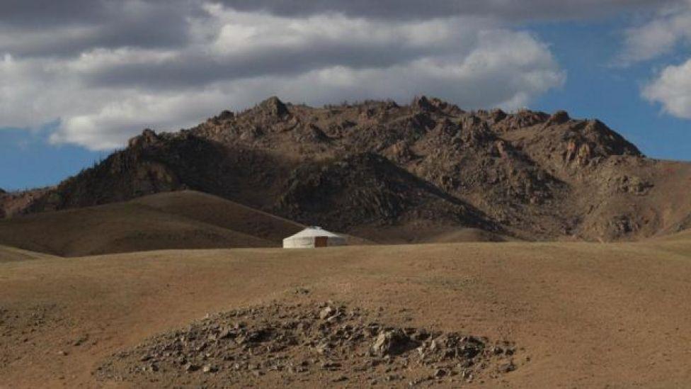 أرض مقفرة في منطقة جبلية تتوسطها خيمة