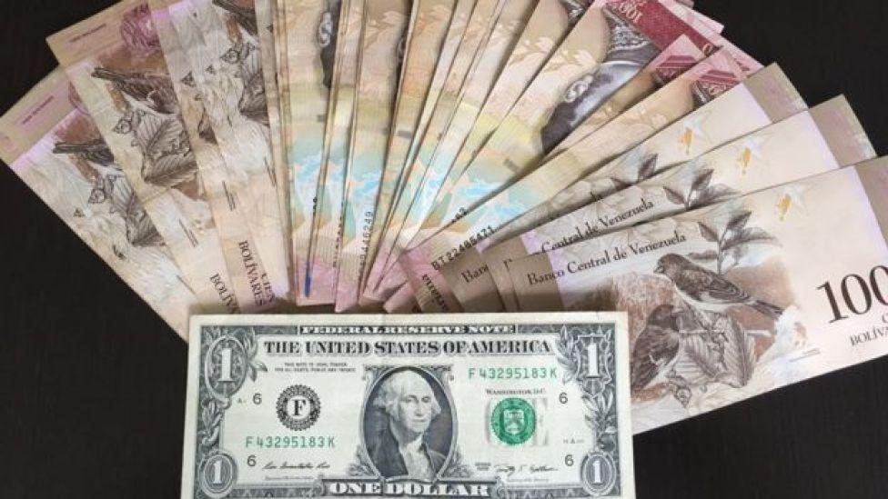 Un billete de dólar y el equivalente en bolívares en el mercado paralelo