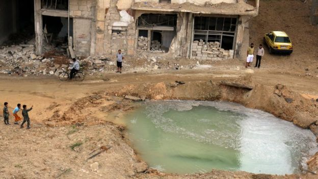 Residents of rebel-held Tariq al-Bab district inspect water-filled crater that activists say was caused by bunker-busting bomb (23 September 2016)