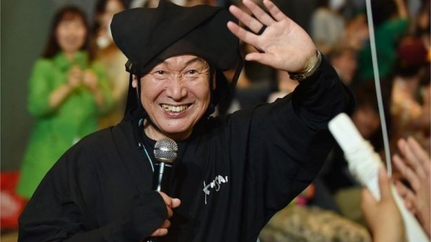 Japanese designer Kansai Yamamoto waves to the audience after his fashion event 'super energy !!' in Tokyo on June 12, 2015.