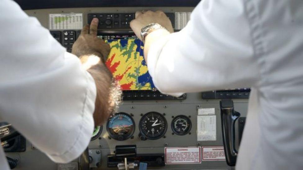 Piloto y copiloto aprietan botones en la cabina del avión.