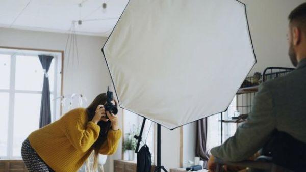فتاة تلتقط صورة احترافية لشاب في غرفة التصوير