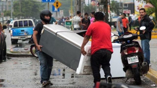 Dos hombres se llevan un refrigerador