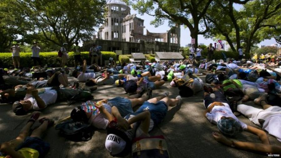 Children perform a die-in in front of the Atomic Bomb Dome in Hiroshima on 5 August 2015