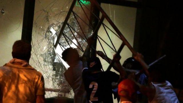 Manifestantes intentan romper una ventana del Congreso.