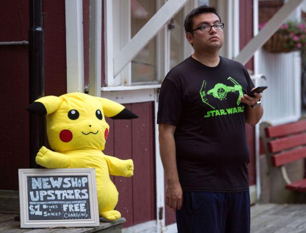 HOmbre con celular en la mano y al fondo un muñeco de Pokémon.
