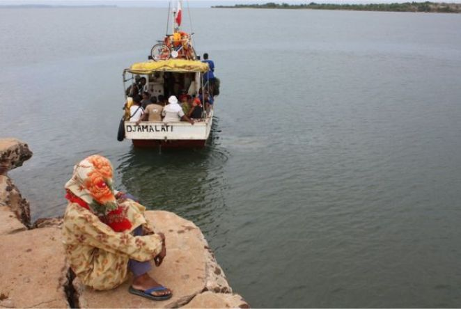 A woman sits on the shore close to a small motorboat - known as a kwassa-kwassa - which is loaded with passengers